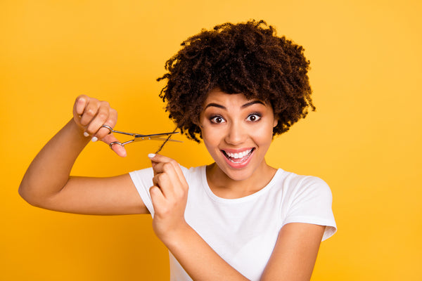 Smiling young woman about to cut her curly hair with a pair of scissors.