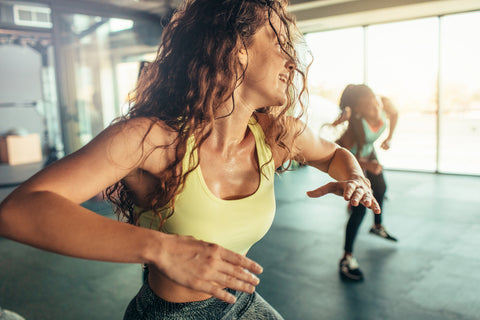Woman with brown curly hair working out in the gym together with other women.