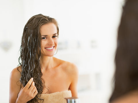 Woman with long hair in front of the mirror and massaging her hair with hair-care products.