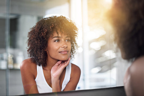 Woman looking in mirror and smiling   plopping RevAir