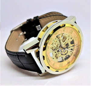 A gold mechanical watch with black leather band and personalized engraving.
