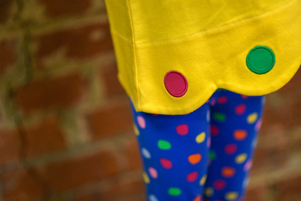 Girl's yellow scalloped tunic with colored circle appliqués