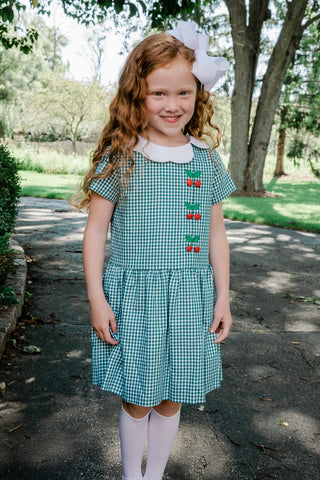 girl outside wearing green gingham dress with berry buttons