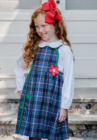 girl in blue plaid jumper with red appliqué flower