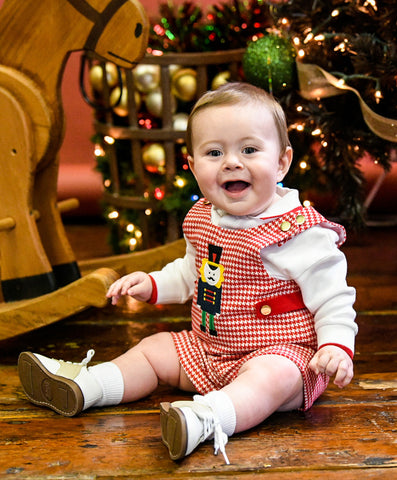 A baby boy in a red houndstooth shortall