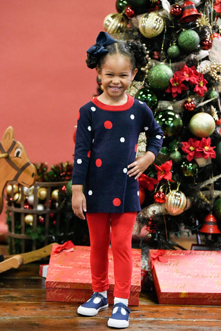 girl in front of a Christmas tree in a polka dot sweater