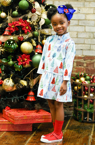 Girl in blue tree dress in front of decorated tree