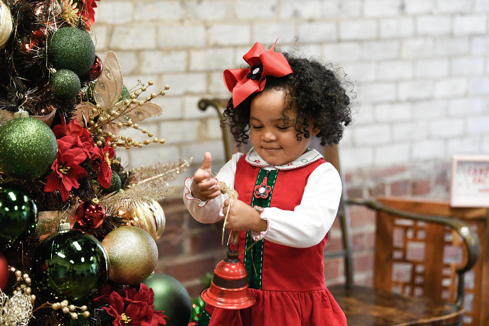 young girl decorating a tree in a holiday dress with matching hair bow