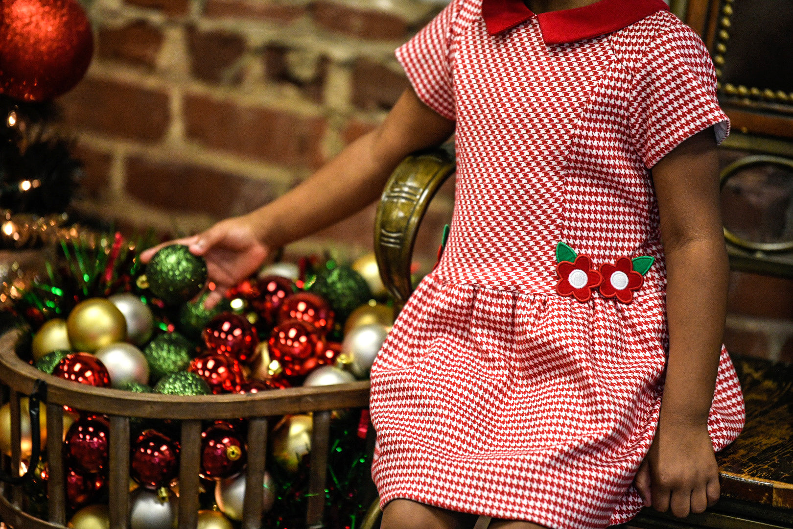 young girl in red houndstooth dress with flower appliqués selecting an ornament