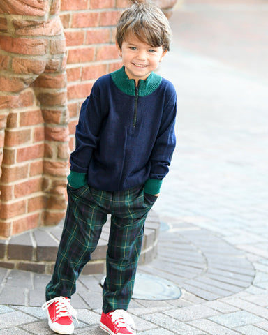 A young boy in a green tartan pant and navy and green sweater
