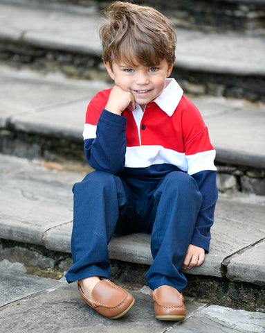 young boy in a red and blue color block polo sitting on stairs