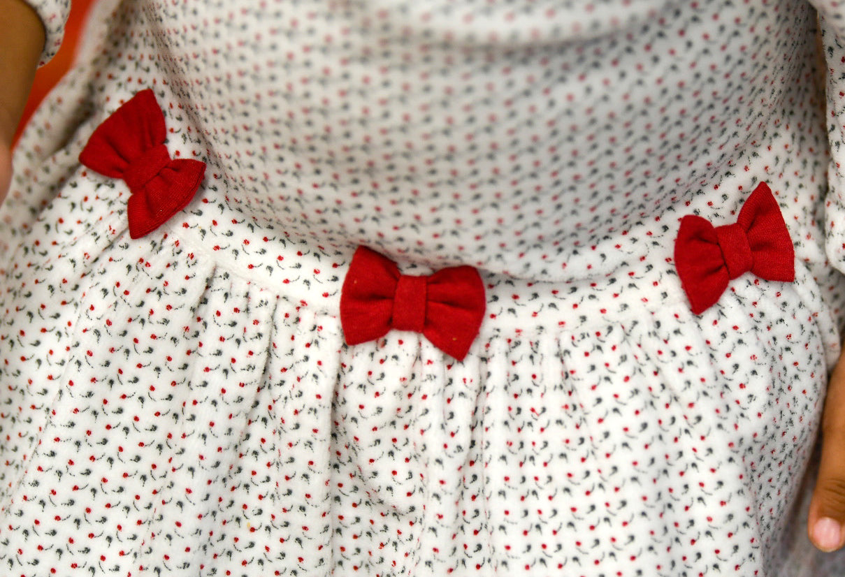 detail of white floral pattern with red bows
