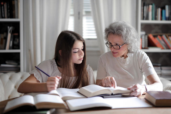 grandmother and granddaughter looking at books