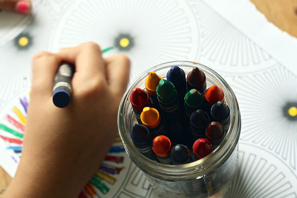 the hand of a child coloring with crayons on paper