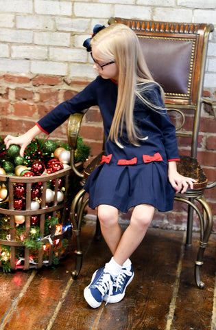 girl sitting in a blue dress with red bows