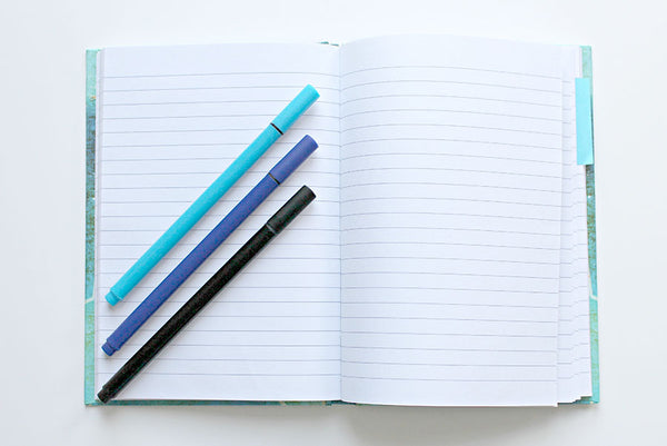 a journal-style book with colorful pens