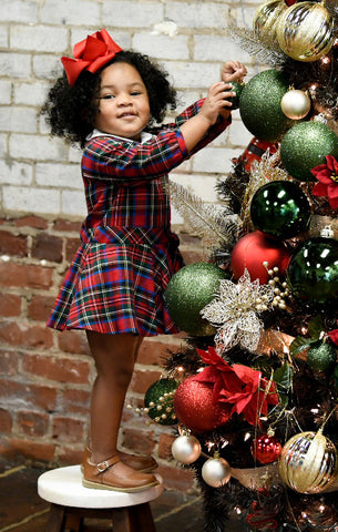 young girl in a plaid dress decorating a tree