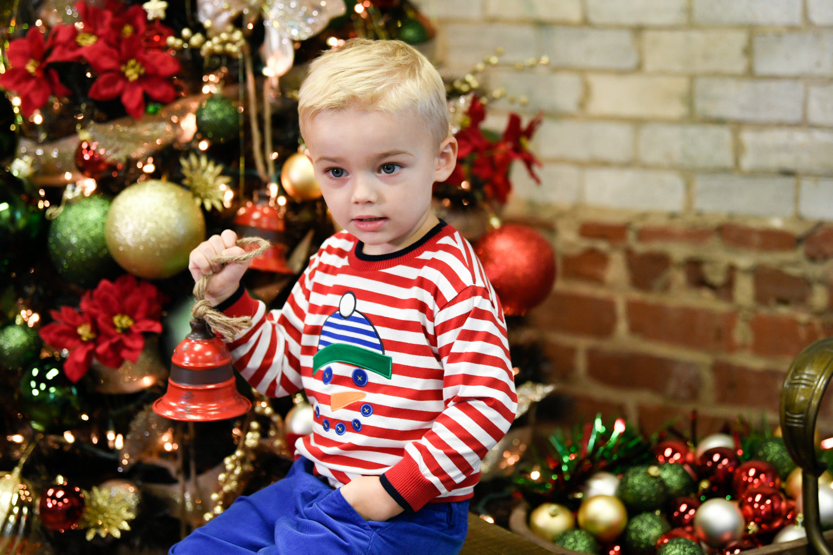 boy holding ornament wearing red and white stripe shirt with snowman