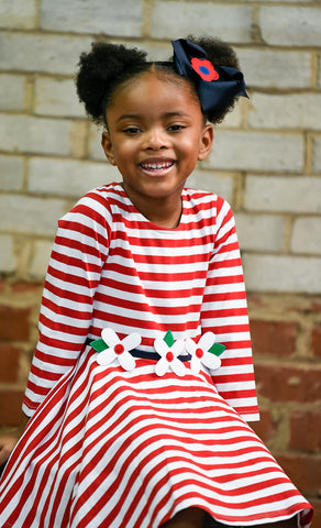 young girl in red and white stripe dress with flowers