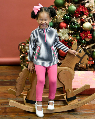 girl on rocking horse in stripe tuinc with pink flowers