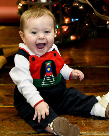 baby boy in train longall smiling