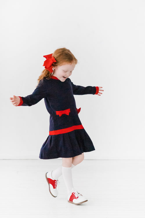 Girls Navy Blue Dress with Red Trim on Model