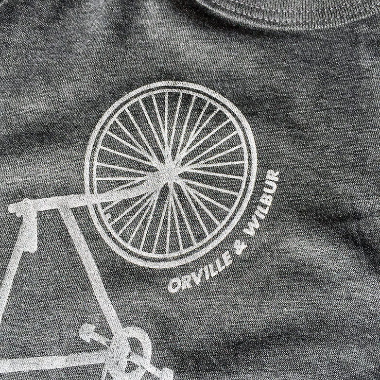 Close up image of Bernoulli Apparel's Baby One Piece with Wright Bicycle design.