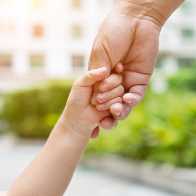 Parent holding child's hand to motivate and encourage