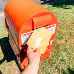 Image of a hand holding a yellow envelope, about to insert the envelope into a bright red mail box by the side of the road.