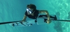 Woman subwinging performing roll under water