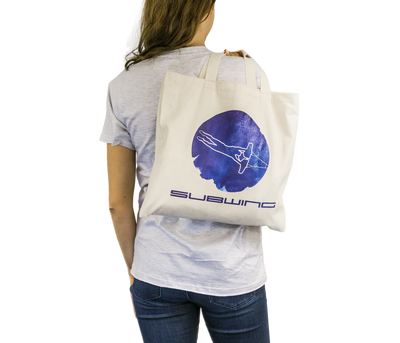Woman holding cotton beach bag with Subwing logo