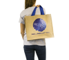 Woman holding jute beach bag with Subwing logo