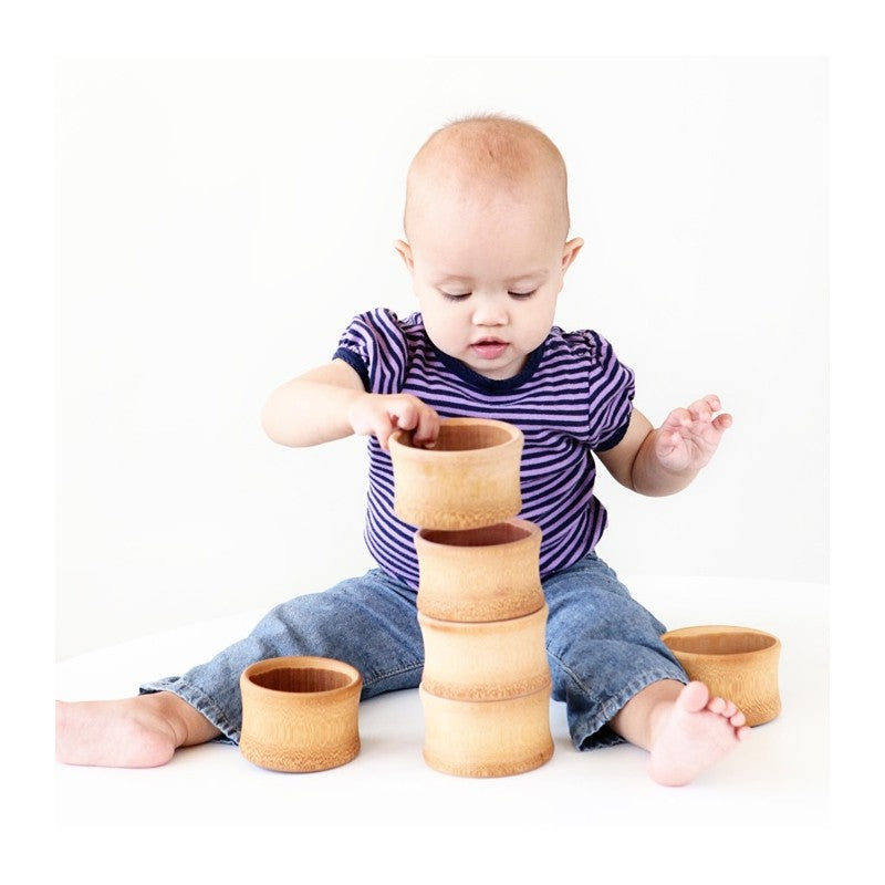 Toddler playing with a stack of Organic Bamboo Baby Feeding Bowls