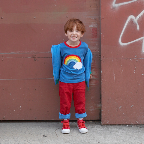 Boy wearing blue organic tshirt with rainbow design