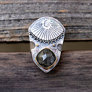 Close up of quartz inclusion evil eye shield ring with high carat gold and silver granulation