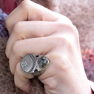 Close up of model wearing rose cut quartz apotropaic shield ring with high carat gold and silver granulation