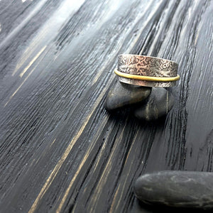19k gold and oxidized silver textured band ring with a botanical pattern. side view