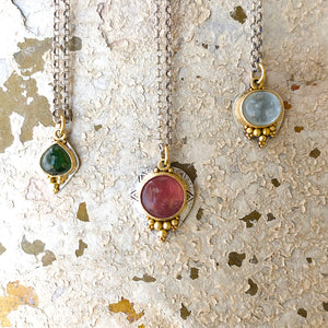 Etruscan style high carat gold and silver pendants with tourmalines. group shot