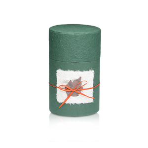 Oval shaped biodegradable cremation urn in green made of hand-crafted papers and available in four sizes.