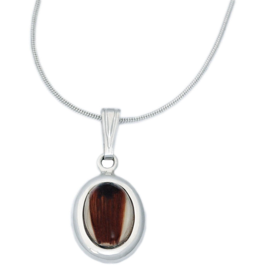 Oval memorial jewelry pendant uses a loved one's cremated remains or lock of hair to fashion handmade mementos that are as unique as the individual.