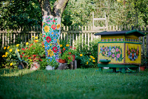 garden view, tree bark and beehive painted in flowery patterns