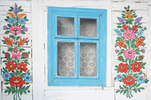 blue cottage window with white walls painted in floral motives