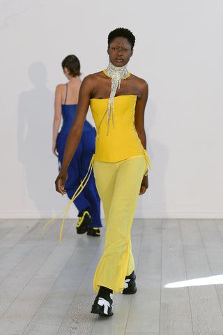 Lula Laora ss22 the garden Getty runway, yellow leather corset top, wide yellow trousers, chain necklace.