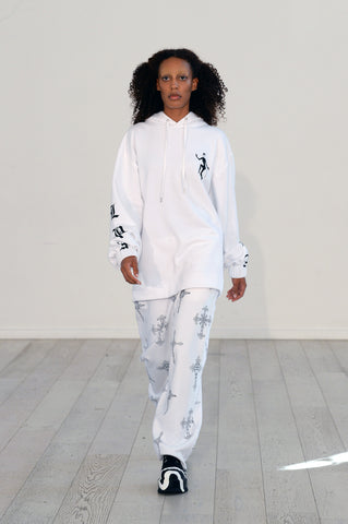 Lula Laora ss22 the garden Getty runway, white hoodie, white joggers/sweatpants with black detailing.
