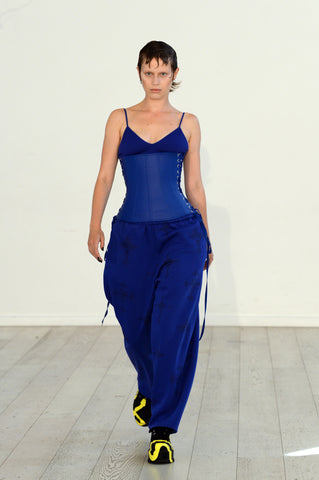 Lula Laora ss22 the garden Getty runway, blue bra, and blue sweatpants with a blue leather corset top.