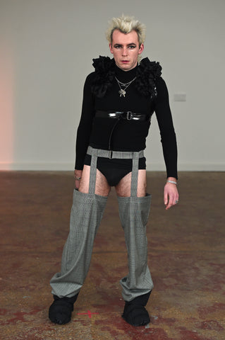 LULA LAORA AW21 Getty Images, menswear model wears a black ruffled harness over a long sleeved black t-shirt and black underwear. He also wears puffy shoes and houndstooth garter trousers.