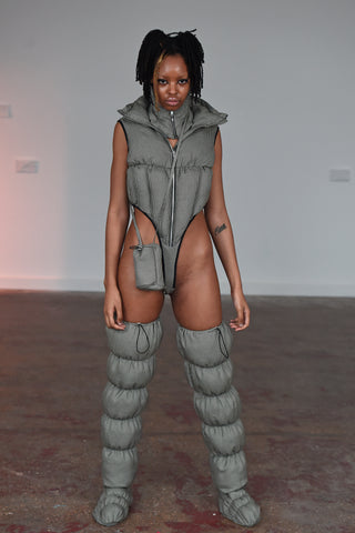 LULA LAORA AW21 Getty Images, womenswear model wears fine houndstooth puffy shoes that are thigh high. She also wears a small houndstooth bag and a puffer jacket bodysuit with a high leg. It has a front zipper.