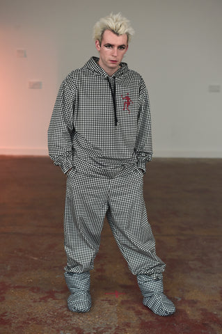 LULA LAORA AW21 Getty Images, menswear model wears a matching track suit in fine houndstooth. The puffy shoes are also houndstooth. The houndstooth hoodie has a Red Devil lady logo.