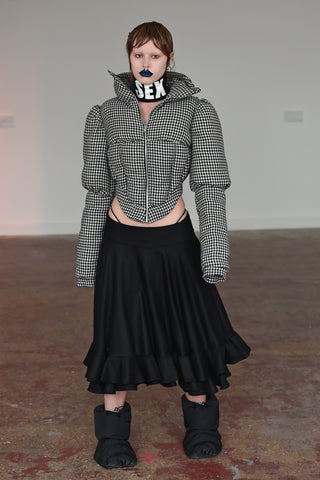 LULA LAORA AW21 Getty Images, womenswear model has blue lips and short hair. She wears a houndstooth puffer jacket and a black midi skirt with black puffer shoes