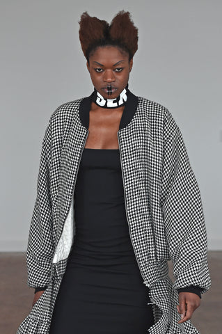 LULA LAORA AW21 Getty Images,black dress with sex necklace collar, model wears a houndstooth long bomber coat.